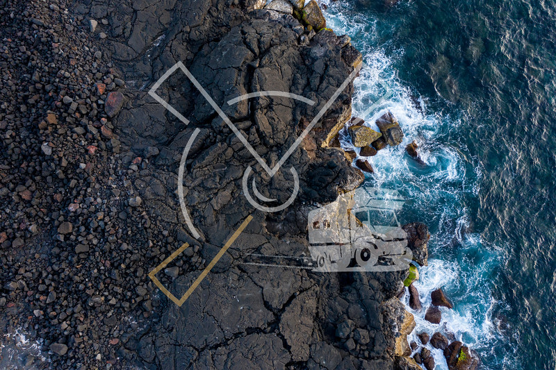aerial image showing the typical black lava basalt coastline of Ilha do Pico Island in the Azores