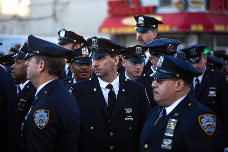 . New York Police Department (NYPD) officers from the 84th precinct stand outside before the funeral of slain NYPD officer Rafael Ramos at the Christ Tabernacle Church December 27, 2014 in the Glenwood section of the Queens borough of New York City. Ramos was shot, along with Police Officer Wenjian Liu while sitting in their patrol car in an ambush attack in Brooklyn on December 20. Thousands of fellow officers, family, friends and Vice President Joseph Biden arrived at the church for the funeral.  (Photo by Kevin Hagen/Getty Images)