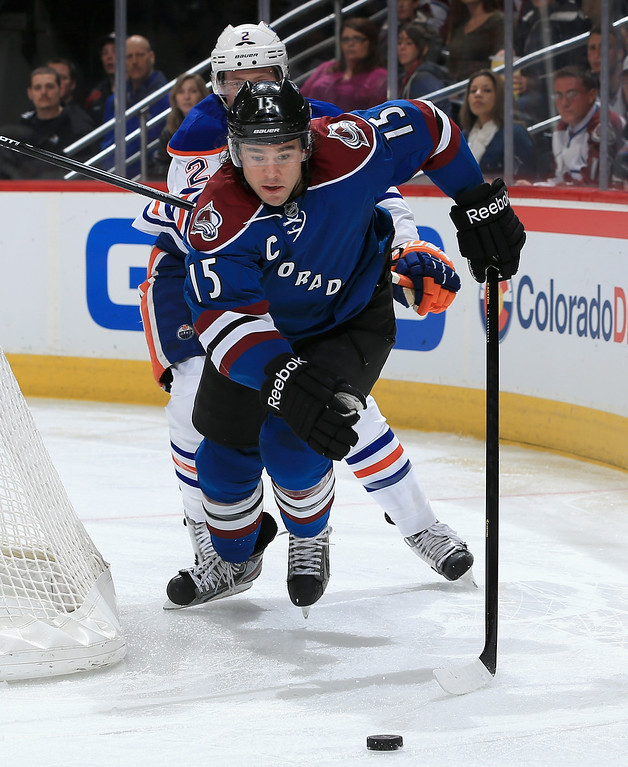 . DENVER, CO - APRIL 19:  P.A. Parenteau #15 of the Colorado Avalanche looks to control the puck against Jeff Petry #2 of the Edmonton Oilers at the Pepsi Center on April 19, 2013 in Denver, Colorado.  (Photo by Doug Pensinger/Getty Images)