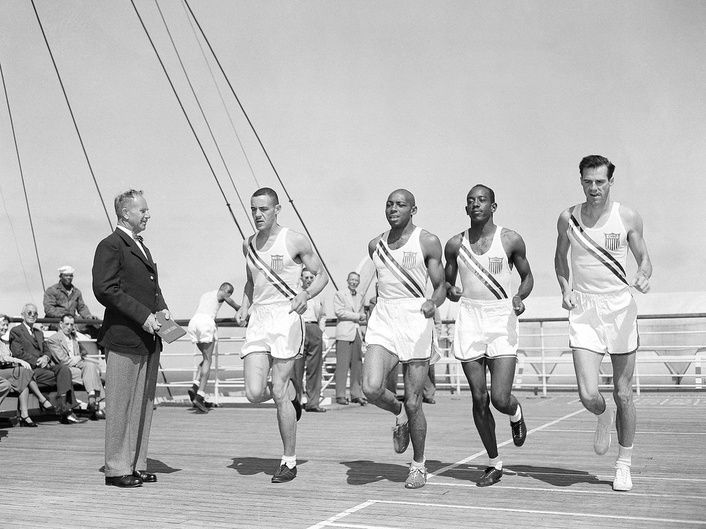 . Head track coach Dean Cromwell (left) of the University of Southern California watches four top American sprinters limber up on a deck of the liner America, on July 22, 1948 during the voyage to England with the U.S. Olympic Team. Sprinters, left to right are: Malvin G. Whitfield, Bay City Tex.; Barney Ewell, Lancaster, PA.; Harrison Dillard Cleveland, O., and Mel Patton, Los Angeles, California. (AP Photo/JDC)