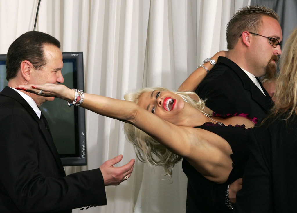 . ** FILE ** Anna Nicole Smith is assisted backstage after posing for photos at the 32nd annual American Music Awards, in this Nov. 14, 2004, file  in Los Angeles. Smith, 39, the former Playboy playmate whose bizarre life careened from marrying an octogenarian billionaire to the untimely death of her son, died Thursday, Feb. 8, 2007, after collapsing at a South Florida hotel, one of her lawyers said. (AP Photo/Reed Saxon, file)