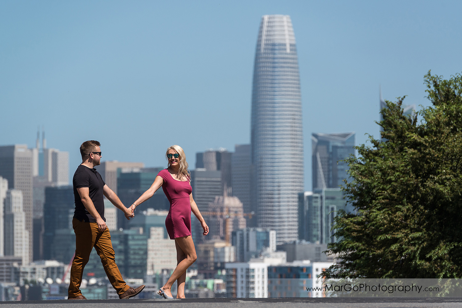 engagement session at Potrero Hill in San Francisco - woman in pink dress and man in black t-shirt and brown jeans walking on the street with amazing downtown SF view