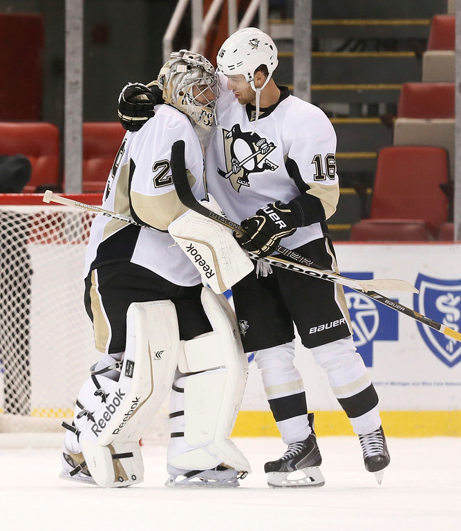 . Pittsburgh Penguins goalie Marc-Andre Fleury (29) is congratulated by Brandon Sutter (16) after beating the Detroit Red Wings 2-0 in a NHL preseason hockey game in Detroit Wednesday, Oct. 1, 2014. (AP Photo/Paul Sancya)