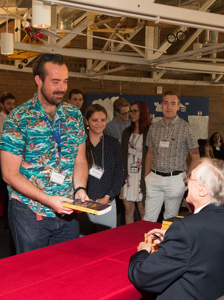 """Seamus Anderson with John Mather, as he signs copies of his book """"The Very First Light"""" -- An award luncheon, """"Dr. John Mather Nobel Scholars Program Award"""", as part of the National Space Grant Foundation. College Park Aviation Museum, College Park, MD, August 2, 2019."""