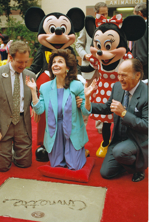 """. Former \""""Mouseketeer\"""" Annette Funicello gets set to put her hands in the cement at Walt Disney Studios Theatre, in Burbank, Calif., as she is honored with the Disney Legend Award, on October 21, 1992. With Funicello is her husband Glen Holt, right, and Jeff Hofman, left, Disney Studios official. (AP Photo/Nick Ut)"""