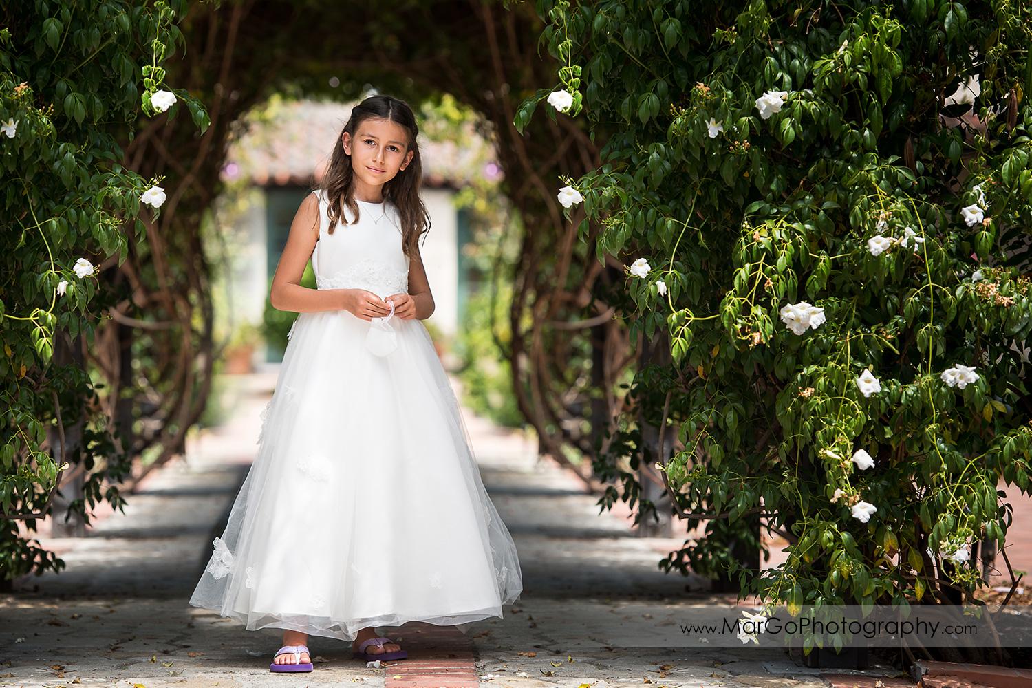 full body portrait of first communion girl in white dress standing under green arch with white flowers at Cafe Wisteria in Menlo Park
