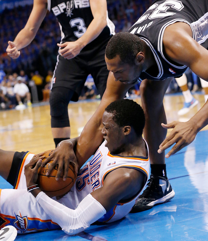 . San Antonio Spurs forward Boris Diaw (33) reaches for the ball held by Oklahoma City Thunder guard Reggie Jackson (15) in the second quarter of Game 3 of an NBA basketball playoff series in the Western Conference finals, Sunday, May 25, 2014, in Oklahoma City. (AP Photo/Sue Ogrocki)