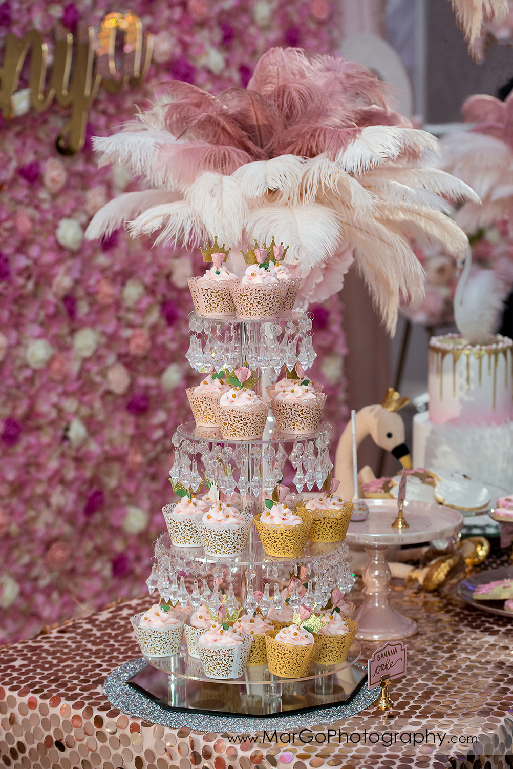 cupcake stand decorated with pink and white feathers at Newark Oasis Palace