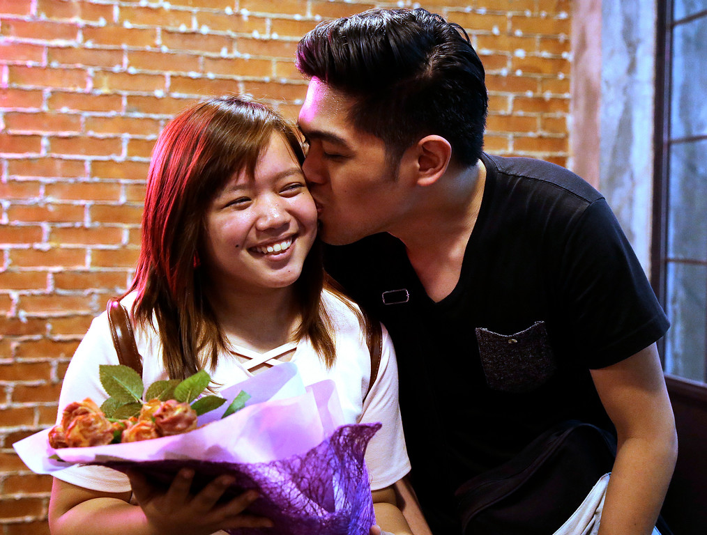 . Mica Alcantara, left, smiles as she is kissed by her boyfriend Richmond Ulap after receiving a bouquet of edible rose shaped bacon at a restaurant which is offering it as part of their Valentines promotion, in Manila, Philippines on Friday, Feb. 10, 2017. A dozen edible rose shaped bacon bouquet costs P2,200 (about US$ 44) and can be delivered to love ones during Valentines Day as an alternative gift to sending real flowers. (AP Photo/Aaron Favila)