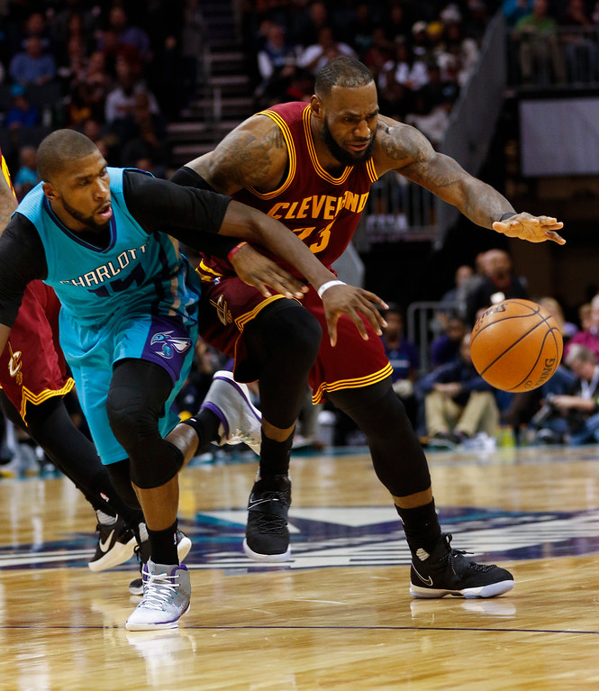 . Cleveland Cavaliers forward LeBron James, right, keeps the ball from Charlotte Hornets forward Michael Kidd-Gilchrist in the second half of an NBA basketball game in Charlotte, N.C., Saturday, Dec. 31, 2016. Cleveland won 121-109. (AP Photo/Nell Redmond)