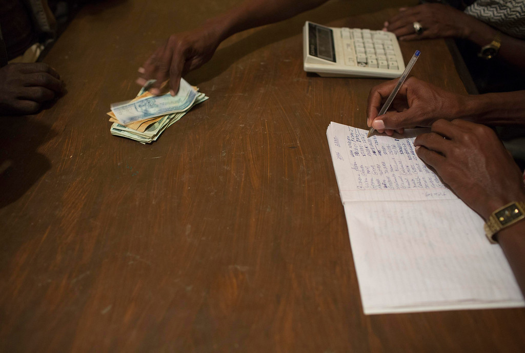 . Members of the Berahile Salt Association pay a merchant after purchasing salt in the town of Berahile in Afar, northern Ethiopia April 19, 2013. The Danakil Depression in Ethiopia is one of the hottest and harshest environments on earth, with an average annual temperature of 94 degrees Fahrenheit (34.4 Celsius). For centuries, merchants have travelled there with caravans of camels to collect salt from the surface of the vast desert basin. The mineral is extracted and shaped into slabs, then loaded onto the animals before being transported back across the desert so that it can be sold around the country. Picture taken April 19, 2013. REUTERS/Siegfried Modola