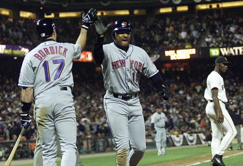 . New York Mets Darryl Hamilton (C) is congratulated by teammate Mike Bordick after scoring the winning run at the top of the 10th against the San Francisco Giants during game two of the National League 2000 Division Series in San Francisco, California 05 October, 2000. The Mets defeated the Giants 5-4 to even the series 1-1.   In the background is Giants reliever Felix Rodriguez.  AFP PHOTO/ John MABANGLO