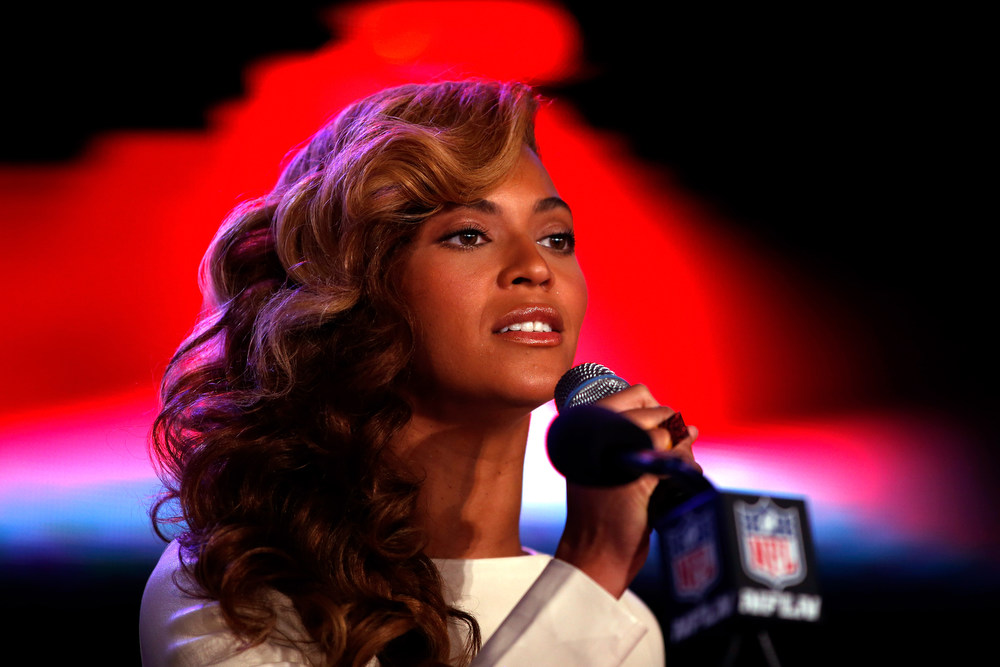 Description of . Singer Beyonce sings the national anthem before she addresses the media during the Pepsi Super Bowl XLVII Halftime Show press conference at the media center on January 31, 2013 in New Orleans, Louisiana. Beyonce will perform at halftime as the San Francisco 49ers will take on the Baltimore Ravens on February 3, 2013 at the Mercedes-Benz Superdome.  (Photo by Scott Halleran/Getty Images)