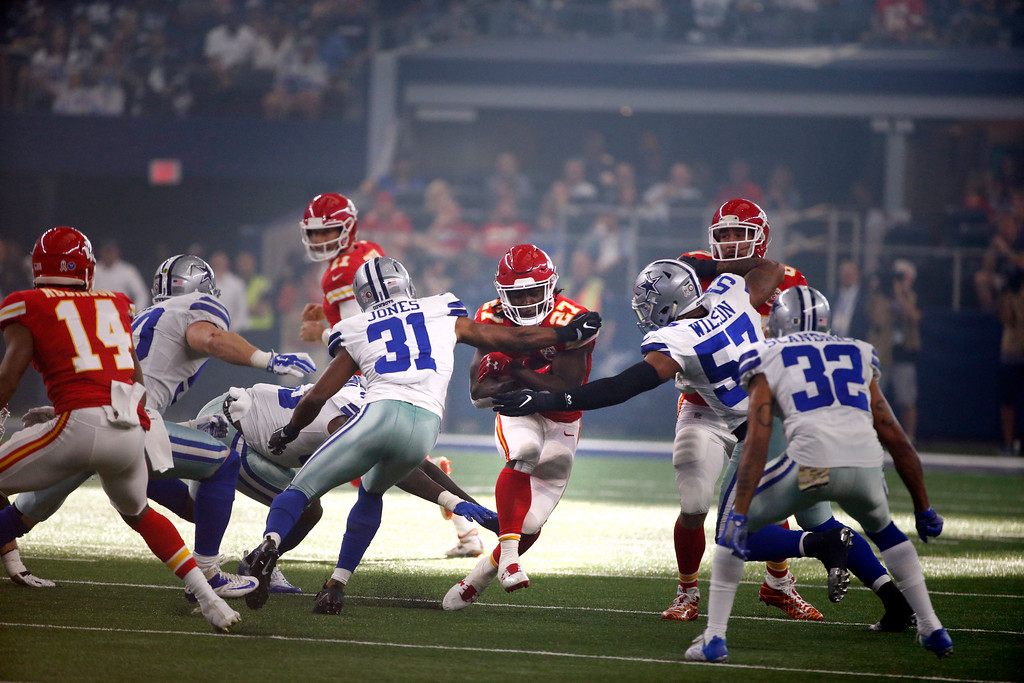 . Dallas Cowboys\' Byron Jones (31) and Damien Wilson (57) attempt to stop Kansas City Chiefs running back Kareem Hunt (27) as he carries the ball during the first half of an NFL football game, Sunday, Nov. 5, 2017, in Arlington, Texas. (AP Photo/Michael Ainsworth)