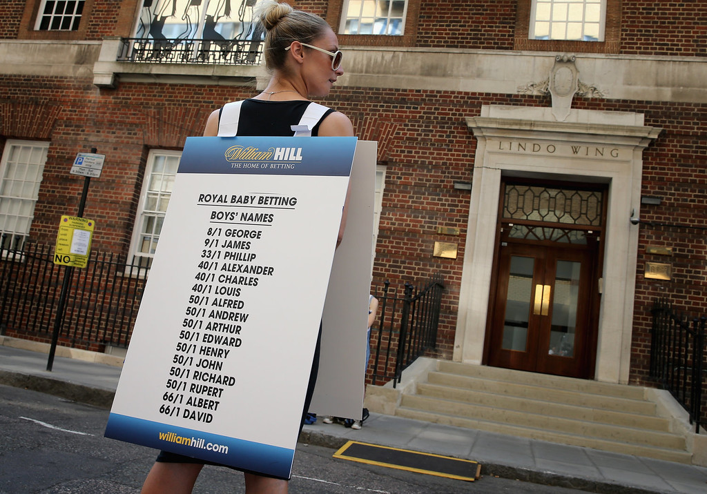 . A girl from a Betting Company wears a board highlighting the latest odds on babies names outside the Lindo wing of St Mary\'s Hospital as the UK prepares for the birth of the first child of The Duke and Duchess of Cambridge on July 16, 2013 in London, England.  (Photo by Chris Jackson/Getty Images)