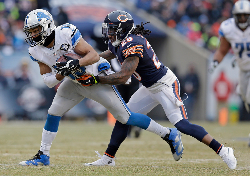 . Detroit Lions receiver Golden Tate (15) makes a catch under pressure from Chicago Bears cornerback Tim Jennings (26) in the second half of an NFL football game Sunday, Dec. 21, 2014, in Chicago. (AP Photo/Nam Y. Huh)