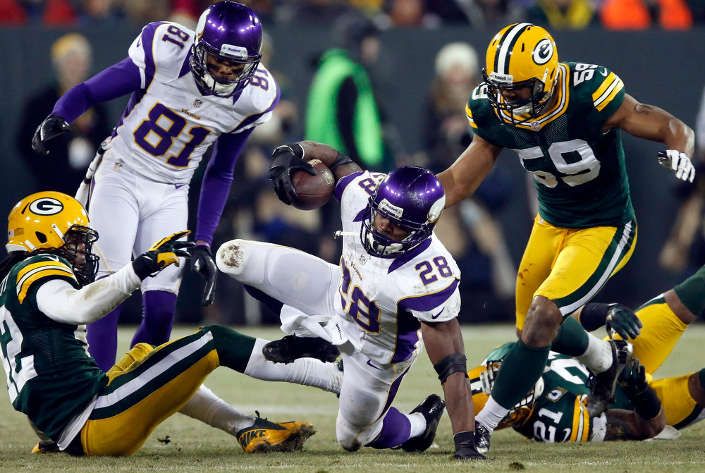 Description of . Minnesota Vikings running back Adrian Peterson (28) is brought down by Green Bay Packers inside linebacker Brad Jones (59) during their NFL NFC wildcard playoff football game in Green Bay, Wisconsin January 5, 2013.  REUTERS/Tom Lynn