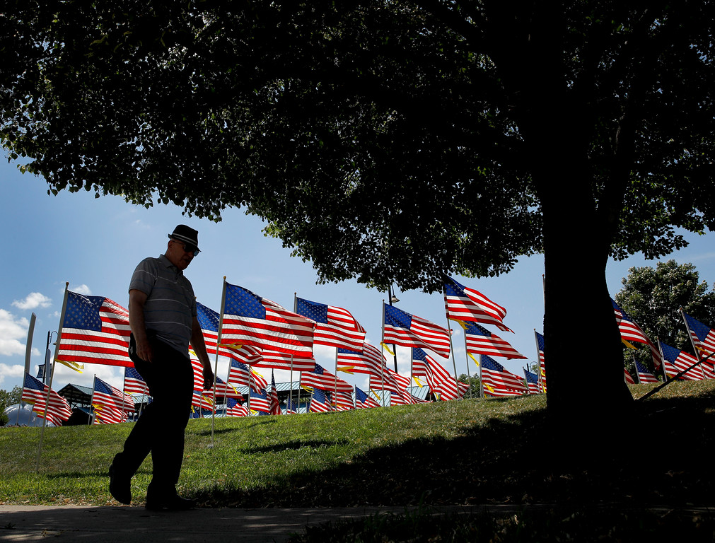. A man walks past U.S. flags on display for Independence Day Wednesday, July 4, 2018, in Merriam, Kan. (AP Photo/Charlie Riedel)