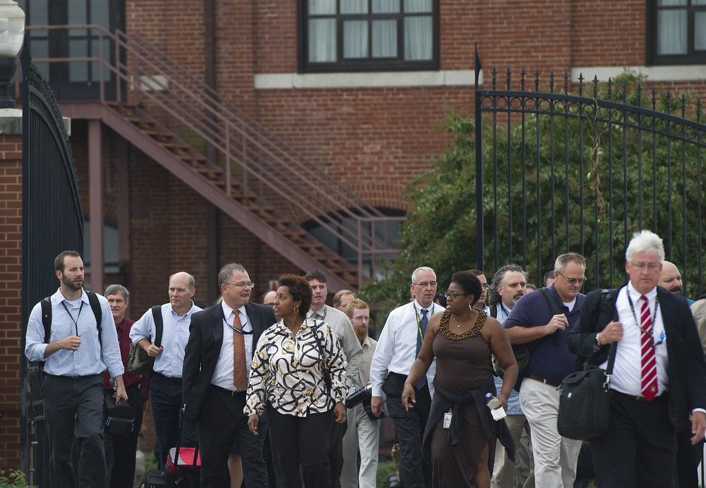 ". Workers who had sheltered in place exit the Navy Yard following a shooting at the Navy Yard in Washington on September 16, 2013. A shooting rampage Monday at a US naval base in the heart of Washington claimed at least 13 lives, including the gunman, while another possible suspect was still at large, police said. The shooting sparked a massive show of force as police and federal agents surrounded the Navy Yard, cordoning off streets only blocks from the US Capitol, home of Congress. US officials gave no indication of any link to terrorism while police said the motive for the attack on the naval installation was unknown. ""At this hour, it appears that we have at least 12 fatalities,\"" Washington DC police chief Cathy Lanier told a press conference.       SAUL LOEB/AFP/Getty Images"