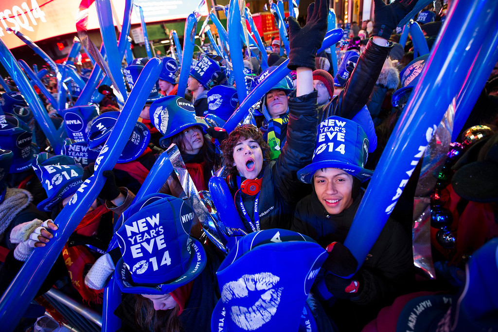 . Joseph Kalamatia, of Brooklyn, N.Y., center, cheers during the New Year\'s Eve celebrations in Times Square, Tuesday, Dec. 31, 2013, in New York. (AP Photo/John Minchillo)