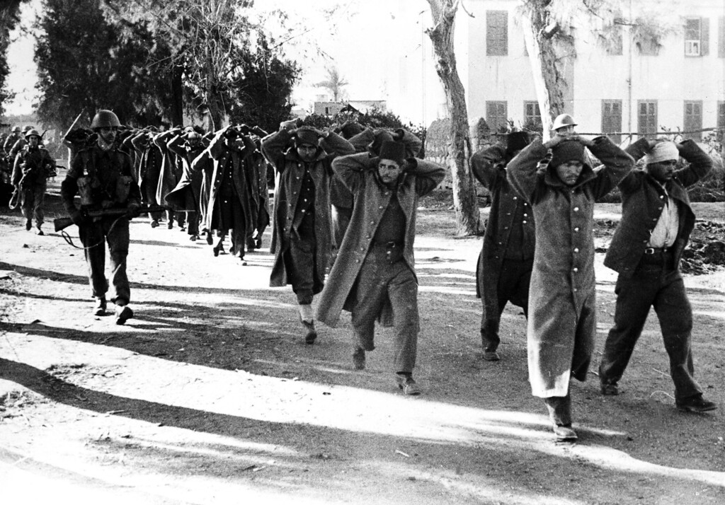 . With their hands on their heads, some of the Egyptian police are escorted by British troops, from the police stations at El-Hamada and Tel-El-Kebir, to the local railway station in El-Hamada, Jan. 16, 1952. The British army were trying to capture guerrillas who had been sniping at British troops. (AP Photo)