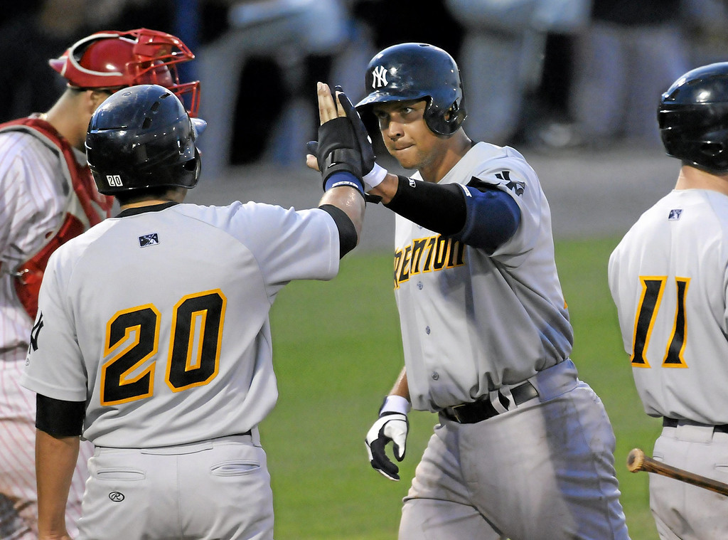 . New York Yankees\' Alex Rodriguez, center, gets a high-five from Ramon Flores (20) after his two-run home run in the fifth inning of a Class AA baseball game with the Trenton Thunder against the Reading Phillies, Monday, July 15, 2013, in Reading, Pa. Rodriguez is doing a rehab assignment with the Thunder recuperating from hip surgery. (AP Photo/Reading Eagle, Jeremy Drey)