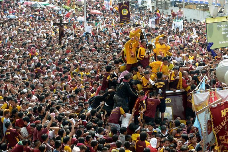 . Catholic devotees jostle for positions as they climb over one another to try to kiss the cross (centre R) draped on the statue of Black Nazarene during the annual procession in honor of the centuries-old icon of Jesus Christ in Manila on January 9, 2013. Masses of Catholic devotees swept through the Philippine capital on January 9 in a spectacular outpouring of passion for a centuries-old icon of Jesus Christ that many believe can perform miracles.   JAY DIRECTO/AFP/Getty Images
