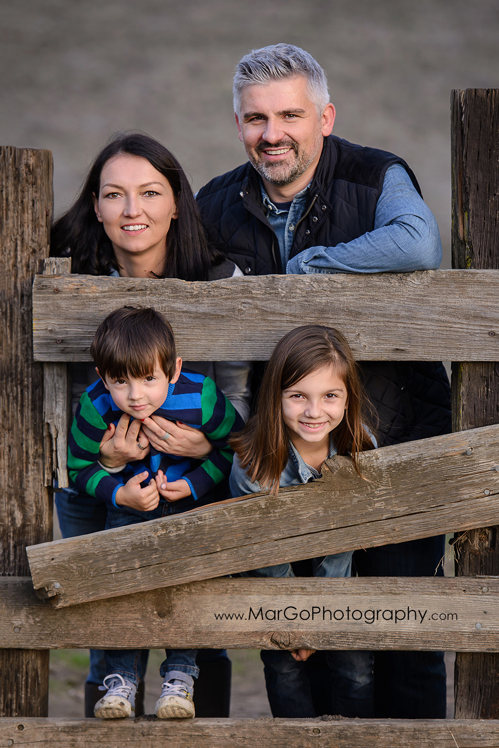 family of 4 in blue and grey clothes leaning against wooden fence during photo session at Old Borges Ranch in Walnut Creek