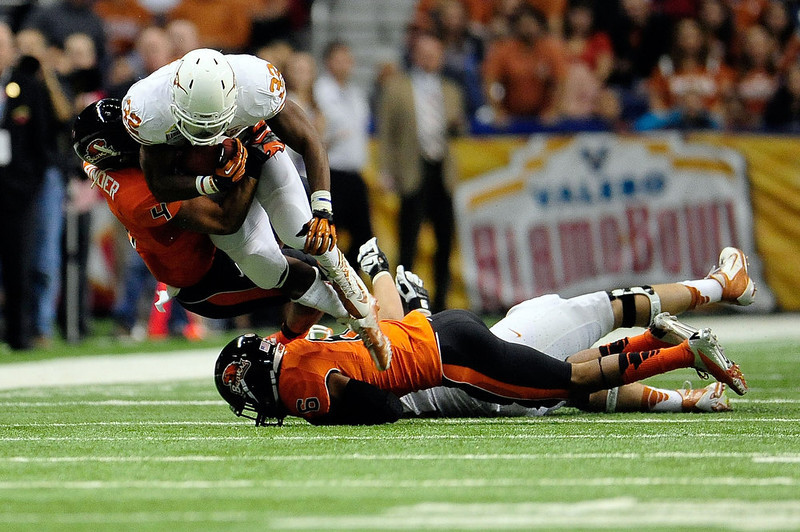 . Johnathan Gray #32 of the University of Texas Longhorns is brought down by D.J. Alexander #4 of the Oregon State Beavers during the Valero Alamo Bowl at the Alamodome on December 29, 2012 in San Antonio, Texas.  (Photo by Stacy Revere/Getty Images)