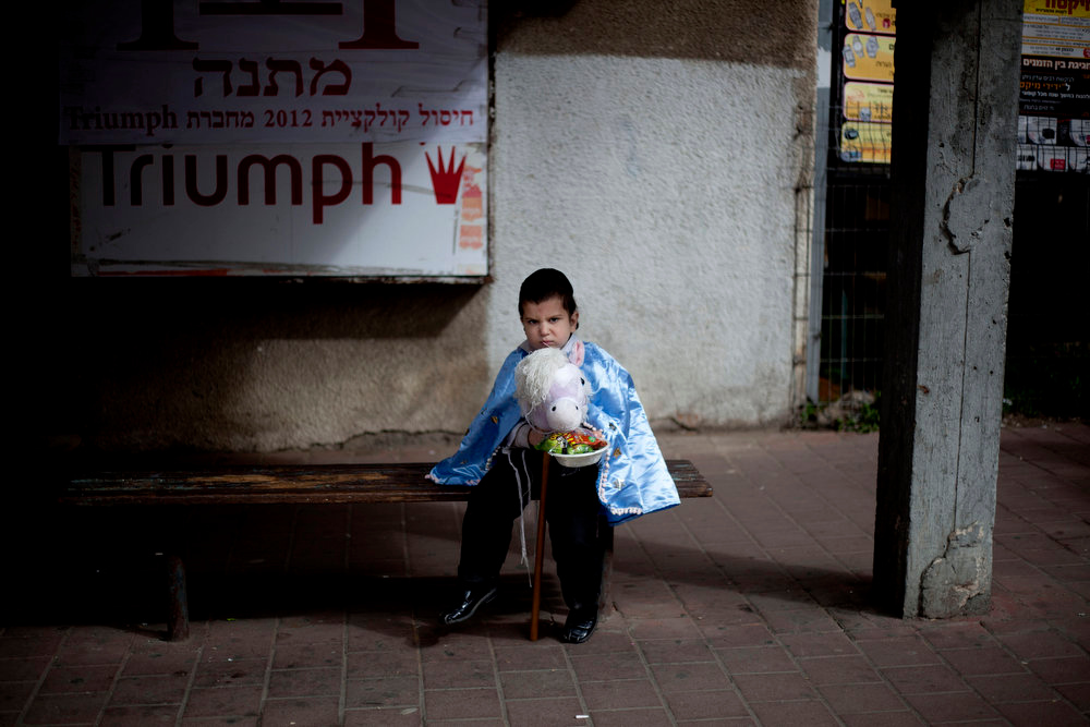 Description of . An Ultra Orthodox Jewish boy wearing a costume, sits on a bench during the Purim festival in the ultra-Orthodox town of Bnei Brak, Israel, Sunday, Feb. 24, 2013. The Jewish holiday of Purim commemorates the Jews\' salvation from genocide in ancient Persia, as recounted in the Book of Esther which is read in synagogues. Other customs include: sending food parcels and giving charity, dressing up in masks and costumes, eating a festive meal, and public celebration. (AP Photo/Ariel Schalit)
