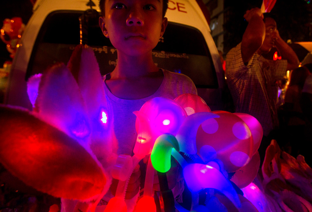 . A boy selling souvenirs waits for customers during the Thadingyut festival in downtown Yangon, Myanmar, Wednesday, Oct. 4, 2017. The Thadingyut festival, also known as lighting festival, is held around the country at the end of Buddhist Lent marking Buddha\'s descent from heaven after He sermonized the Abhidamma to His mother who was born in heaven. (AP Photo/Thein Zaw)