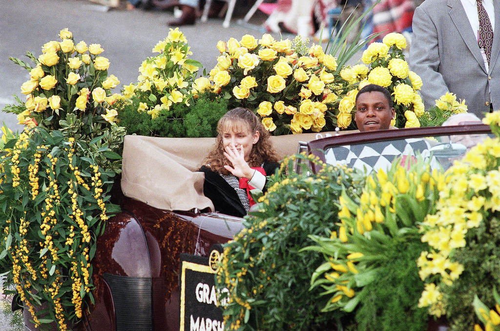 . Olympic gold medal winners Shannon Miller, left, and Carl Lewis, right, greet spectators along Colorado Boulevard in Pasadena, Calif., during the 108th Tournament of Rose Parade on Wednesday, Jan. 1, 1997. Miller and Lewis were parade co-grand marshals. (AP Photo/Damian Dovarganes)