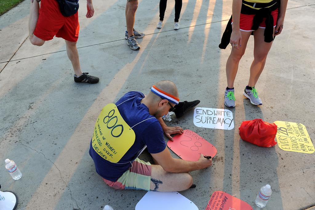""". A protesters writes a sign before jogging through Westwood on a \""""Smash White Supremacy Fun Run,\"""" Thursday, July 18, 2013. (Michael Owen Baker/L.A. Daily News)"""