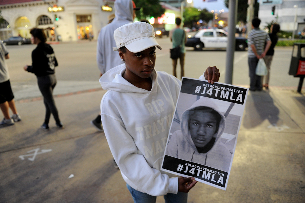 """. Camille Miller holds a picture of Trayvon Martin following a \""""Smash White Supremacy Fun Run\"""" in Westwood, Thursday, July 18, 2013. (Michael Owen Baker/L.A. Daily News)"""