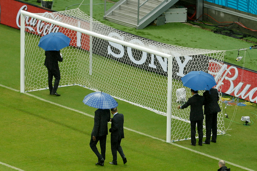 . The referees check out the goal prior to the group G World Cup soccer match between the USA and Germany at the Arena Pernambuco in Recife, Brazil, Thursday, June 26, 2014. (AP Photo/Hassan Ammar)