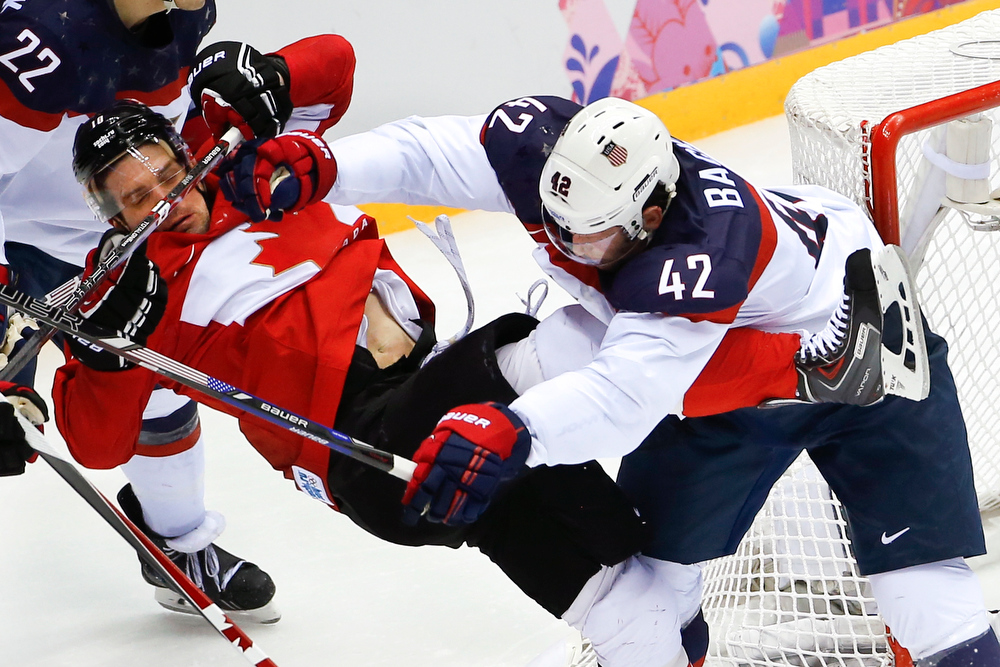 . USA forward David Backes mixes it up with Canada forward Patrick Sharp during the second period of the men\'s semifinal ice hockey game at the 2014 Winter Olympics, Friday, Feb. 21, 2014, in Sochi, Russia. (AP Photo/Matt Slocum)