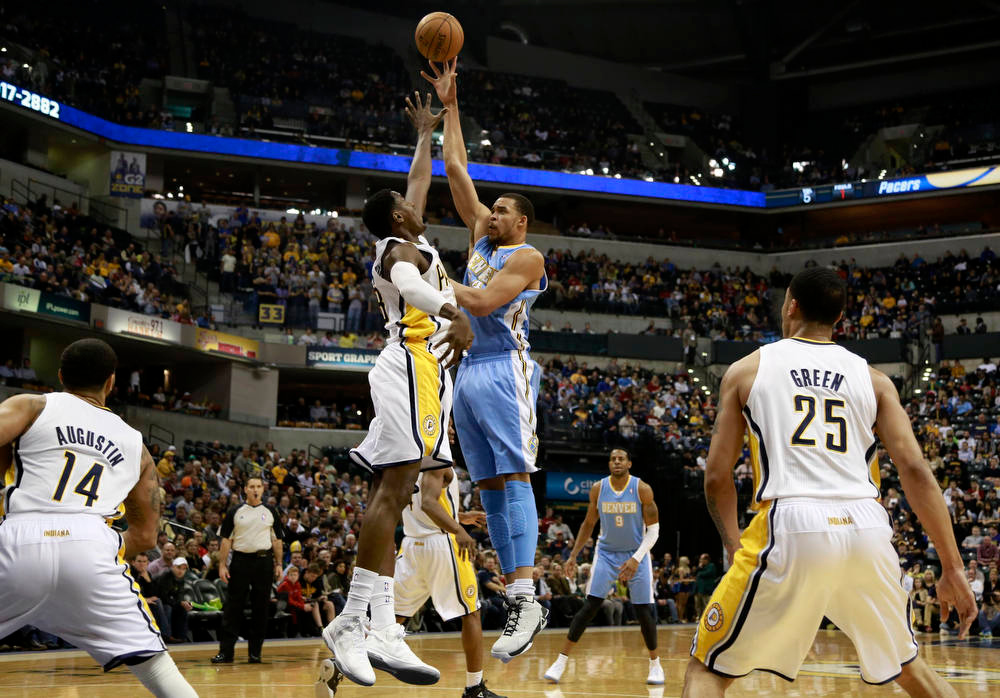 . Denver Nuggets center LaVale McGee shoots the basketball defended by Indiana Pacers center Ian Mahinmi of France while Pacers guard D.J. Augustin (14), Pacers forward Gerald Green (25) and Nuggets forward Andre Iguodala (9) watch during the third quarter of an NBA basketball game in Indianapolis, Indiana December 7, 2012.  REUTERS/Brent Smith