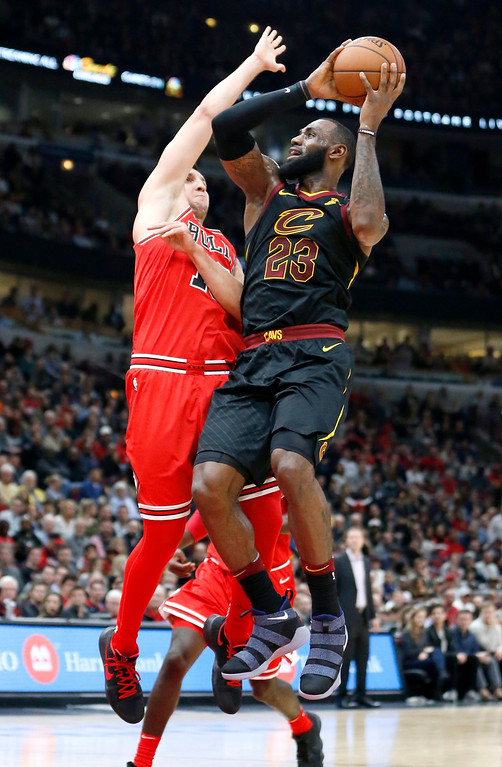 . Cleveland Cavaliers\' LeBron James, right, shoots over Chicago Bulls\' Paul Zipser during the first half of an NBA basketball game Monday, Dec. 4, 2017, in Chicago. (AP Photo/Charles Rex Arbogast)