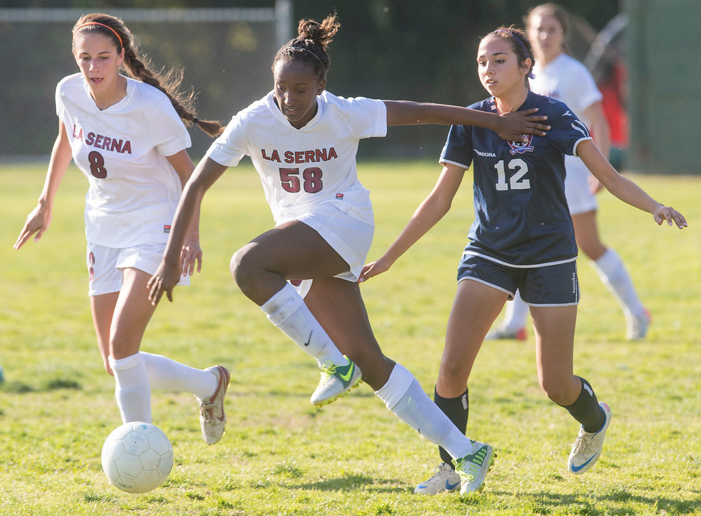 . La Serna High\'s Moriah Earley, center, dribbles the ball vs La Quinta High\'s Valeria Mendez-Mondragon during their Division 5 semifinal matchup Feb. 26, 2013.  (SGVN/Staff photo by Leo Jarzomb)