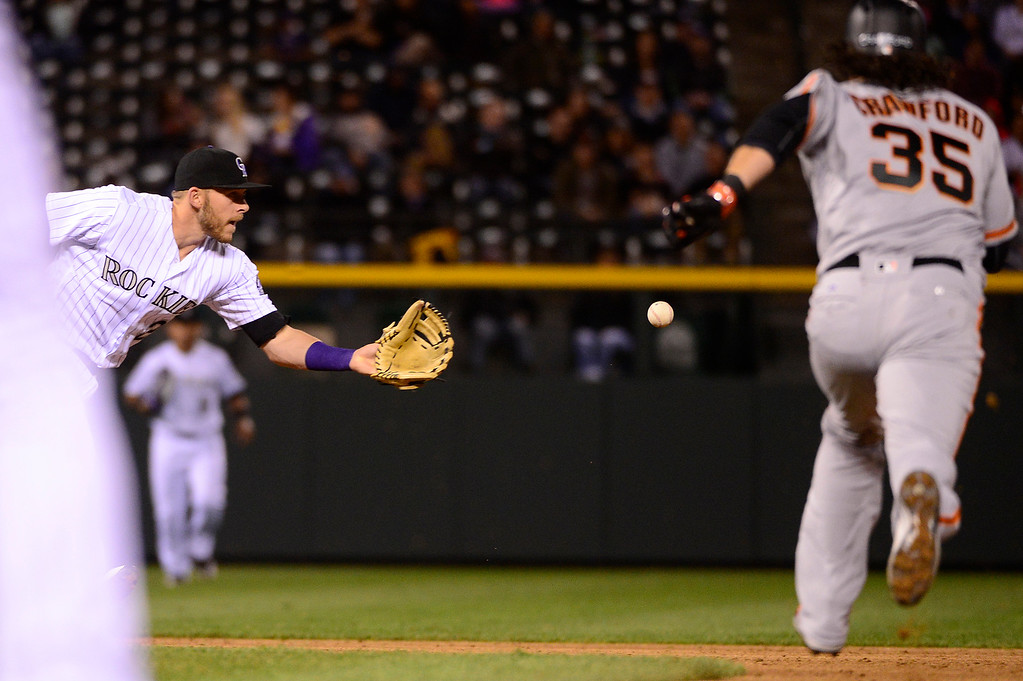 . DENVER, CO - APRIL 12: Colorado Rockies shortstop Trevor Story (27) makes a toss to Colorado Rockies second baseman DJ LeMahieu (9) to tag out San Francisco Giants shortstop Brandon Crawford (35) during the sixth inning at Coors Field on April 12, 2016 in Denver, Colorado. (Photo by Brent Lewis/The Denver Post)