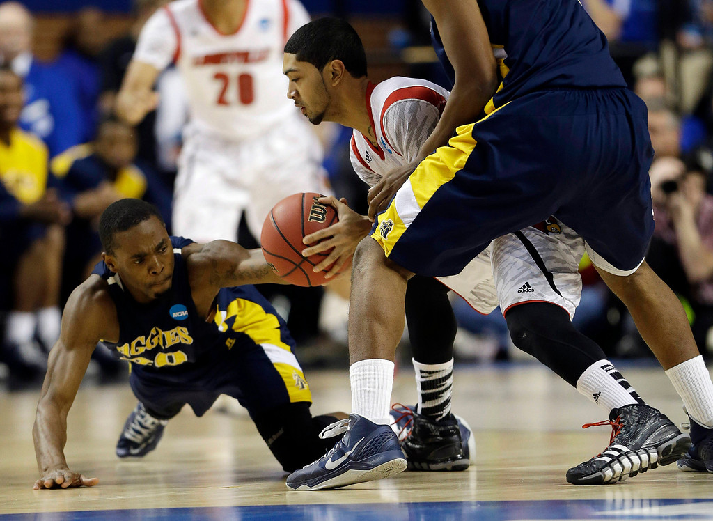 . North Carolina A&T guard Lamont Middleton (30) tries to steal the ball from Louisville guard Peyton Siva (3) during the first half of their second-round NCAA college basketball tournament game, Thursday, March 21, 2013, in Lexington, Ky. (AP Photo/John Bazemore)
