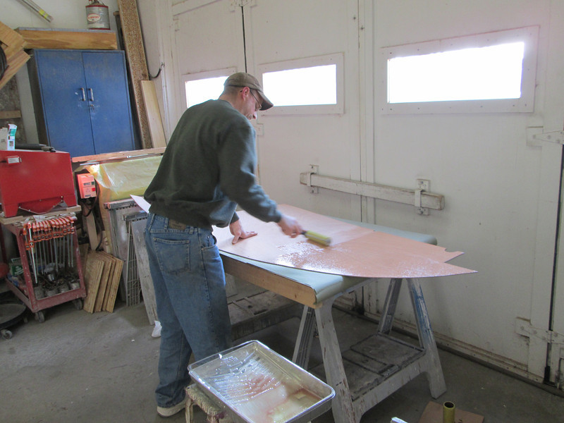 Applying epoxy to the bottom side of the port deck plywood.