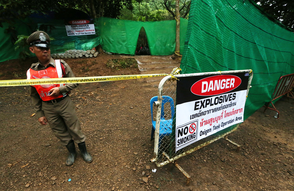 . Thai police stand guard near a cave where 12 boys and their soccer coach have been trapped since June 23, in Mae Sai, Chiang Rai province, in northern Thailand Sunday, July 8, 2018. Thai authorities are racing to pump out water from the flooded cave before more rains are forecast to hit the northern region. (AP Photo/Sakchai Lalit)