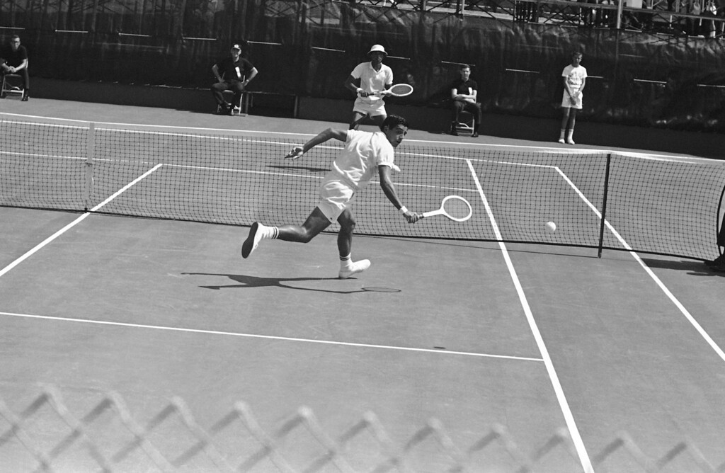 . Arthur Ashe, American Davis Cup player, background, watches his opponent Rafael Osuna, Mexican Davis Cup player, dash after ball during their match in Dallas, Texas on July 31, 1965, in the American Zone finals. Ashe defeated Osuna, 6-2, 6-3, 9-7. (AP Photo/Ferd Kaufman)