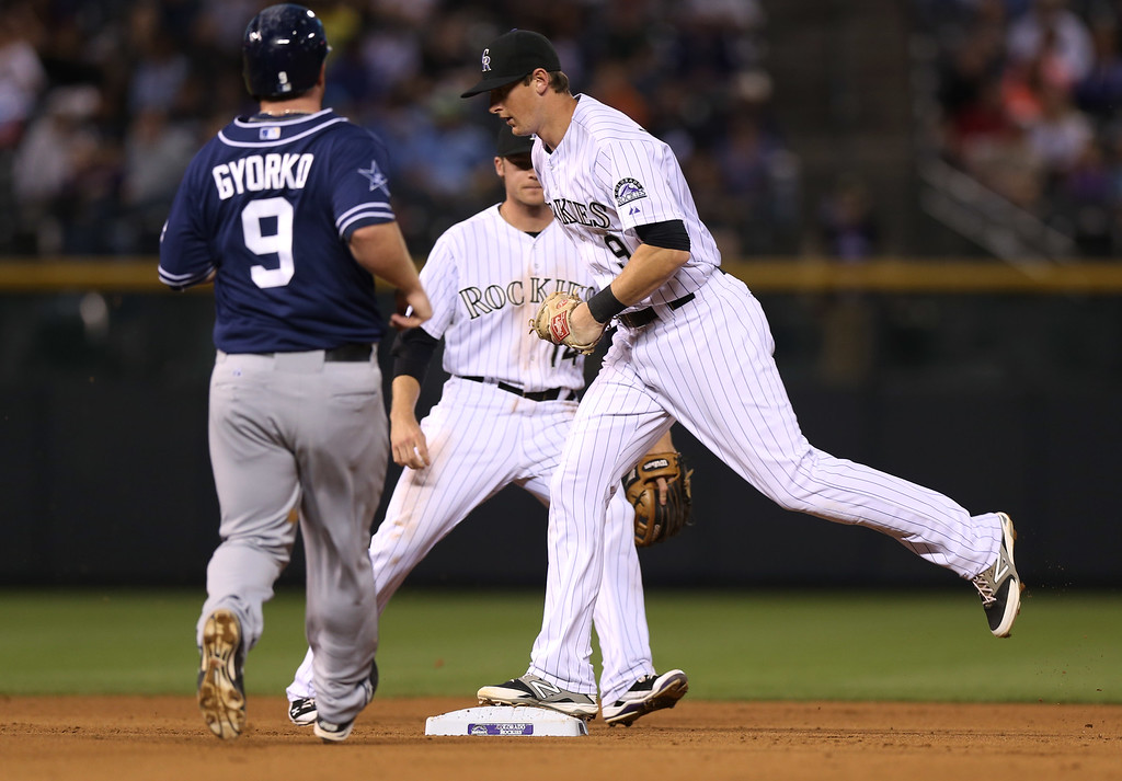 . Colorado Rockies second baseman DJ LeMahieu, right, steps on second base to force out San Diego Padres\' Jedd Gyorko, left, as Rockies shortstop Josh Rutledge looks on to end the top of the fourth inning of a baseball game in Denver on Saturday, Sept. 6, 2014. (AP Photo/David Zalubowski)