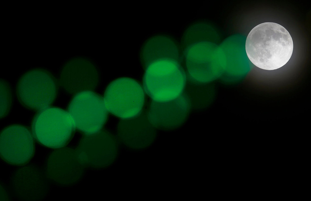 ". A full moon rises through a hazy sky past a string of green lights on Saturday, June 22, 2013, in Baltimore. The moon, which will reach its full stage on Sunday, is expected to be 13.5 percent closer to earth during a phenomenon known as ""super moon\"". (AP Photo/Patrick Semansky)"