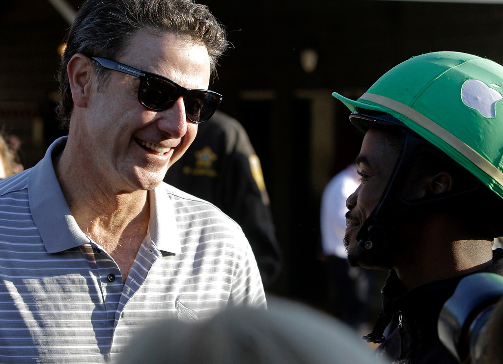 . Part-owner of Kentucky Derby hopeful Goldencents Rick Pitino, left, talks to jockey Kevin Krigger at Churchill Downs Wednesday, May 1, 2013, in Louisville, Ky. (AP Photo/Garry Jones)