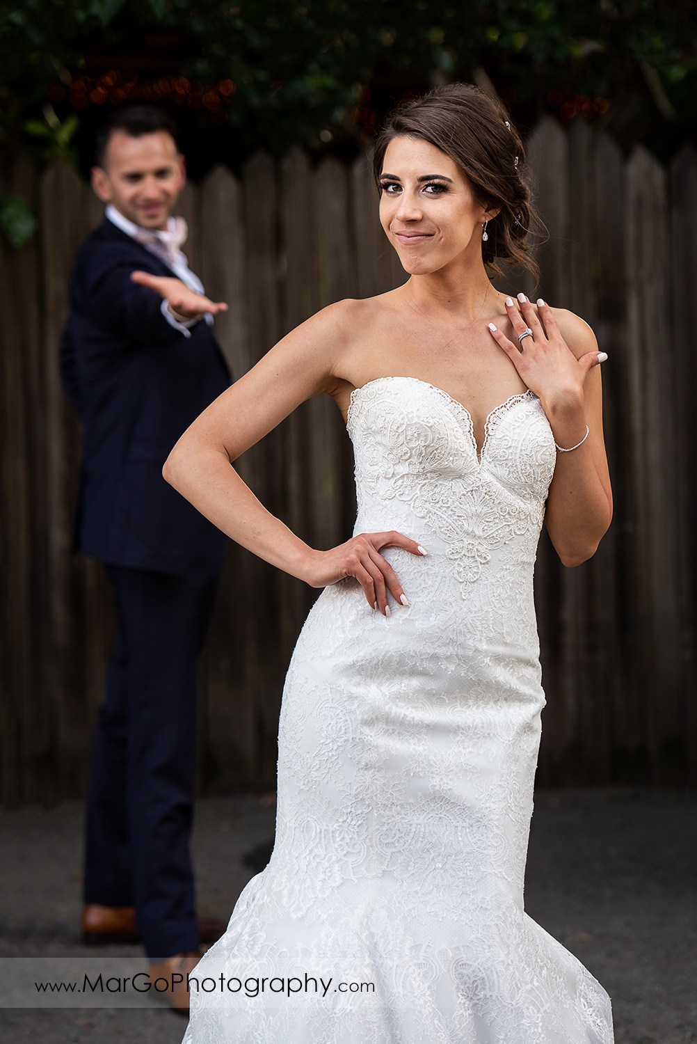 portrait of bride showing wedding ring with groom in background at San Pablo Rockefeller Lodge