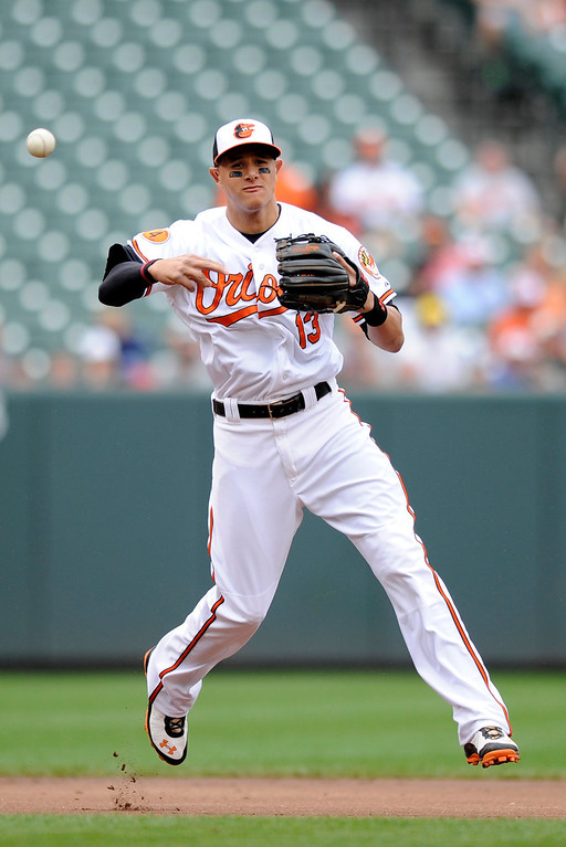 . Baltimore Orioles third baseman Manny Machado throws to first to get out Colorado Rockies\' DJ LeMahieu during the third inning of a baseball game on Sunday, Aug. 18, 2013, in Baltimore. (AP Photo/Nick Wass)