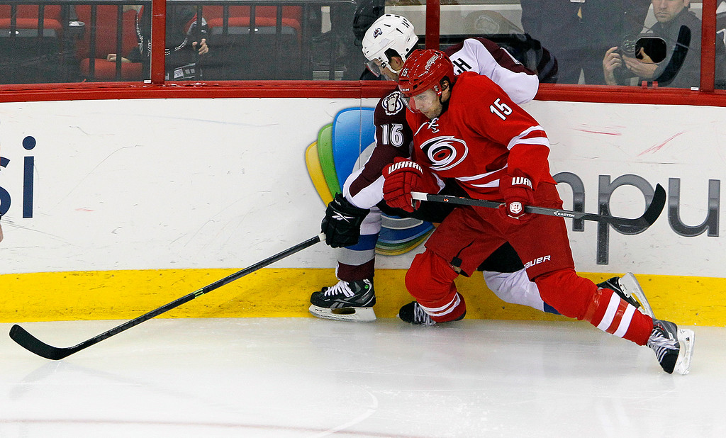 . Carolina Hurricanes\' Tuomo Ruutu (15), of Finland, checks Colorado Avalanche\'s Cory Sarich (16) into the boards during the third period of an NHL hockey game in Raleigh, N.C., Tuesday, Nov. 12, 2013. (AP Photo/Karl B DeBlaker)